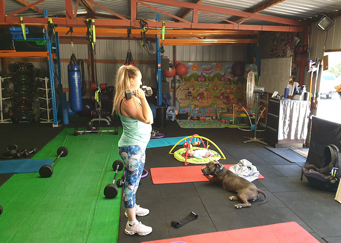 A woman lifting weights in the Back to Basics 4 Life Fitness Studio with dog by her side - pets welcome!