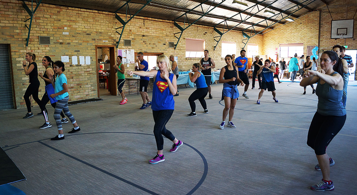 A community fitness event in a hall with women and men including kids working out together and getting active