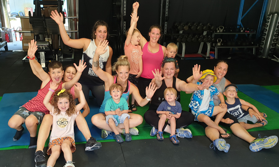 Parents and their kids all smiling after a group fitness workout in child friendly studio