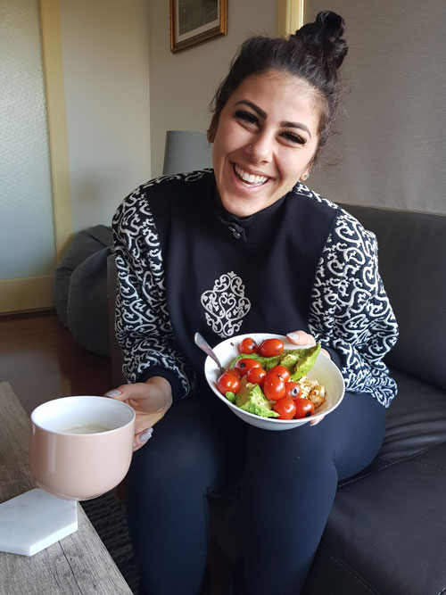 Shadi sits on couch with her hand holding a bowl of delicious salad ready to enjoy for lunch as part of a good balanced diet