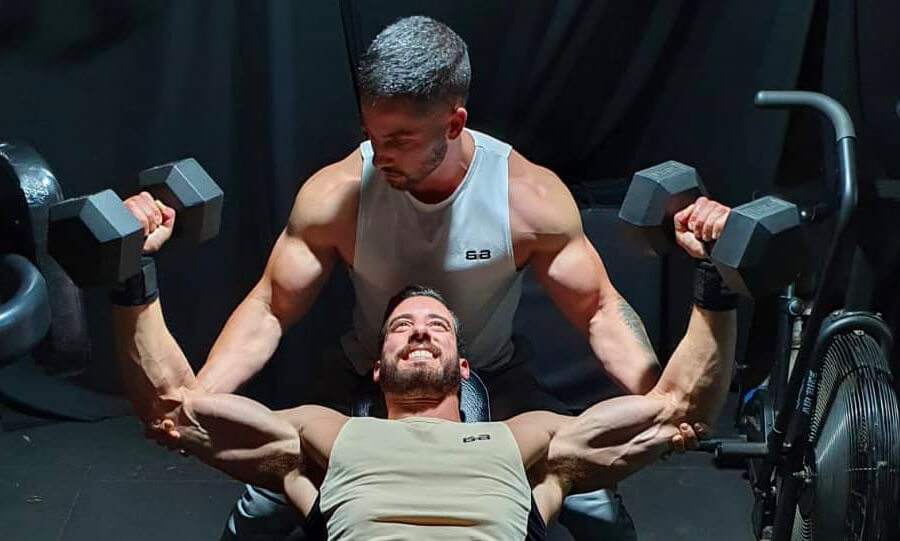Male personal gym trainer supporting male with weight lifting in studio Melbourne
